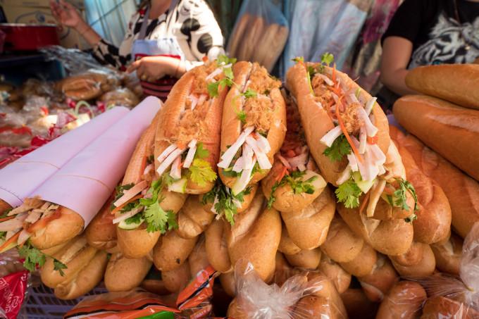 Khao Jee Pa-TaCòn gọi là bánh mì Lào. Người bán sẽ cắt bánh mì theo chiều dọc, sau đó phết lên một lớp pate dày và béo ngậy, rồi thêm vào đó xúc xích nướng, dưa chuột, hành lá, cà rốt, củ cả muối và ruốc thịt cùng lớp nước sốt cay ngọt. Nhiều du khách cho biết, với họ món bánh mì ngon nhất này có thể tìm thấy ở chợ Khua Din, Vientiane. Ảnh: Migrationology