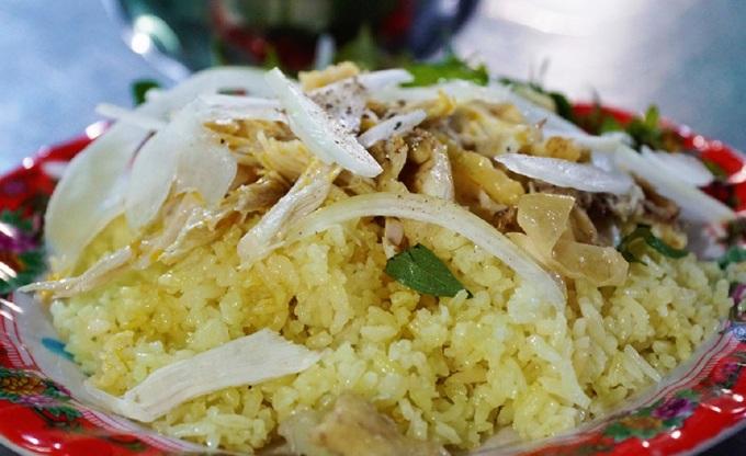 Cơm gà nổi tiếng ở các địa phương như Hội An, Tam Kỳ (Quảng Nam), núi Nhạn (Phú Yên) có đặc trưng là hạt cơm khô, rời, không bị bở. Nước luộc gà dùng để nấu cơm nên hạt cơm ánh vàng tự nhiên, căng mịn và ngọt đượm vị gà. Gà luộc chín tới, lọc lấy thịt, xé phay và bóp gỏi cùng hành tây, hành phi, muối, chanh, rau răm. Chén canh cải nấu với gừng tươi là thành phần hỗ trợ tuyệt vời làm tôn thêm hương vị đĩa cơm gà. Ảnh: Di Vỹ