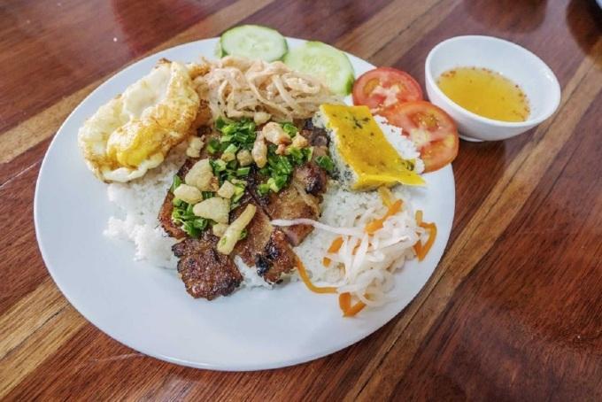 Cơm tấm Sài Gòn là món ăn quen thuộc có mặt ở khắp nơi tại Sài Gòn, có thể dùng làm điểm tâm, cơm trưa, bữa tối đều được. Dĩa cơm sà, bì, chưởng đúng điệu được nấu bằng loại gạo tấm, hạt cơm nhỏ, tơi, xốp không nhão, thêm đồ chua như rau muống, củ cải trắng, dưa leo, bên trên là miếng sườn nướng, bì, chả thơm phức. Người thích ăn trứng có thể gọi thêm miếng trứng ốp la chiên phồng. Thịt sườn nướng được ướp mật ong nên không bị khô, chả mềm và đậm vị, bì được phủ lớp thính thơm và chan mỡ hành béo, khi ăn rưới thêm miếng nước mắm pha hơi sánh là đã có bữa cơm ngon miệng. Ảnh: Shutterstock