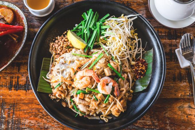 Pad Thai là một trong những món ăn chính của người dân. Đây là một món mì gạo chiên/xào truyền thống, với thành phần gồm có mì gạo xào với trứng và đậu phụ, cùng ớt đỏ, bột me, nước mắm và đường thốt nốt. Đĩa mì được trộn cùng lạc rang giã nhỏ, tôm, tỏi hoặc hẹ tây. Ảnh: Asian inspirations