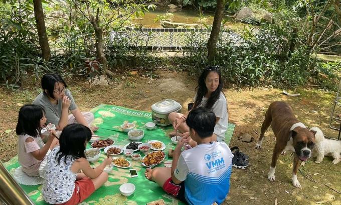 Chị Thủy và các bé ăn cơm ngay dưới tán cây. Ảnh: NVCC