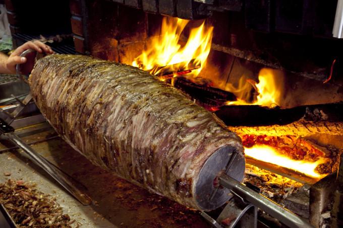Thịt được nướng theo kiểu xoay tròn, được dùng dao thái mỏng theo chiều dọc và kẹp vào giữa bánh mì hình tam giác, cùng rau và các loại nước sốt. Ảnh: Circle Istanbul