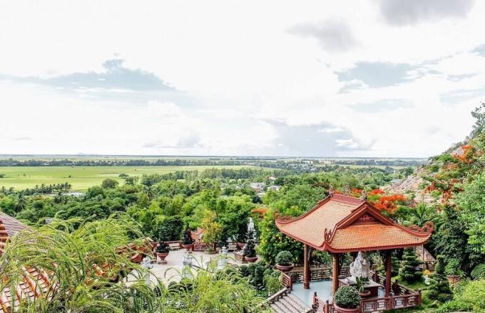 Mùa hè chùa Hang rực trong sắc phượng vĩ, mùa mưa lại nhuộm tím màu bằng lăng. Ảnh: Văn Thái