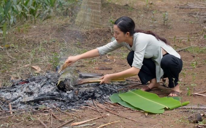 Duyên dùng lá chuối tươi đựng gà sau khi nướng xong, lớp đất sét bọc bên ngoài gà vẫn còn nóng nên phải cẩn thận.